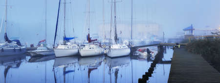 Sailing boats moored to a pier in a thick white morning fog at sunrise, close-up. Yacht club in Kiel, Germany. Sport, recreation, transportation theme