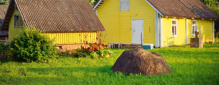 Yellow modern rustic wooden house and old well close-up. Green birch tree forest in the background. Rural landscape. Setomaa, Estonia