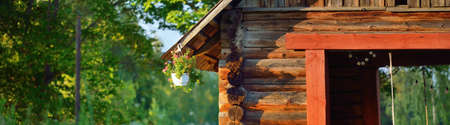 An old traditional rustic wooden house (log cabin or shed) in a green birch tree forest. Pastoral landscape. Garden equipment in the background. Eco tourism, recreation theme. Setomaa, Estonia