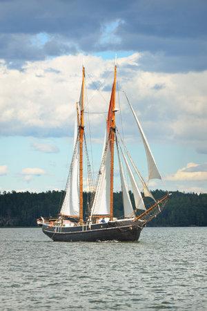 An elegant two-masted gaff schooner (training tall ship) sailing in Mälaren lake, Sweden. Travel, history, traditions, transportation, sailing, sport, cruise, regatta, teamwork. Panoramic view