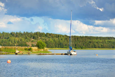 Sloop rigged yacht moored to a pier near the forest lakeshore. Balsta, Mälaren lake, Sweden. Summer vacations, tourism, yachting, recreation, sport, leisure activity, lifestyle