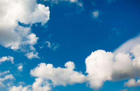 A blue sky with white fluffy cumulus clouds photo