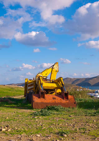 bulldozer in the background of sky with clouds and green hills photo