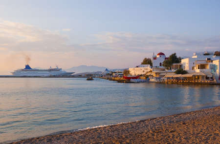 Sunset on Mykonos Island - the ship in port, a famous tavern and a church  photo