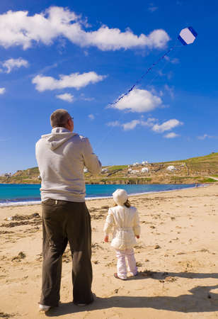 A little girl and dad run a kite in the sky with clouds on the beach near the sea photo