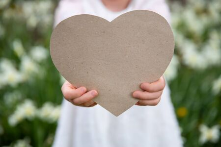 The girl gives a paper heart for Mother's Day, Father's Day, birthday, apology among flowers