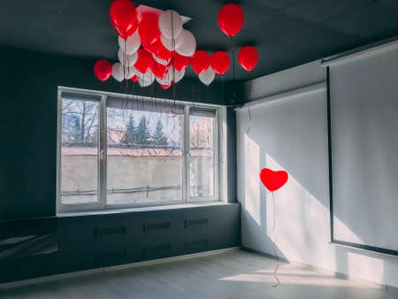 Forever along stand out red heart shape balloon in office below othe balloons. Be special Valentine concept