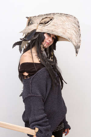 Beautiful girl dressed in witch or shaman halloween costume with black feathers and crow head on the white background with shadows 스톡 콘텐츠