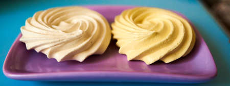 Set of cakes in white and yellow on a purple plate
