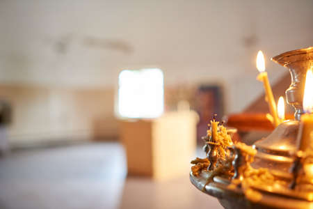 Church candlestick with burning out candles on blurred background. An extinguished candle, a lot of wax dripped.