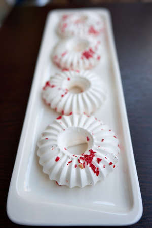 Four white meringue cakes with red pastry crumb sprinkles. Close-up. Selective focus Stock Photo