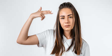 I'm fed up with this. Stylish European girl with long chestnut hair shoots in temple, tilts head, dressed in casual t shirt, demonstrates gesture, isolated on white background