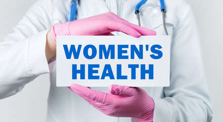 Cropped view of young female doctor in a white coat and pink sterile gloves holding a card with text WOMEN'S HEALTH. Medical concept.