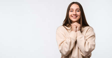 Young happy brunette woman keeps hands together near chin, smiles gently, has cute expression, looking at camera, wearing stylish beige hoodie