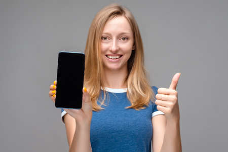 Young beautiful blonde woman showing screen of smartphone over isolated background happy with big smile doing OK sign, thumb up with fingers, excellent sign 스톡 콘텐츠