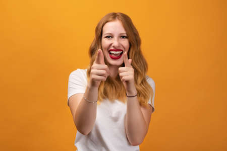 Excited girl with wavy redhead, wearing white t-shirt holding fingers in a finger gun gesture and aims at the camera. Being lucky, isolated over yellow background