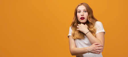 I'm afraid. Fright, phobia, panic attack, horror. Portrait of the scared girl with wavy redhead, wearing white t-shirt, isolated on yellow background. Copy space for your text Stock fotó