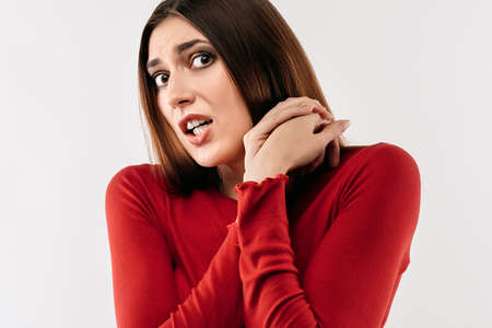 I'm afraid. Image of young scared woman with long chestnut hair in casual red sweater. Fright, phobia, panic attack, horror and facial expression concept. Studio shot, white background Stock fotó