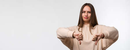 Young woman with long chestnut hair, dressed in casual clothes, looking unhappy and angry, showing thumbs down and expressing dislike. Human emotions concept. Copy space for your text