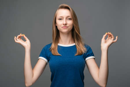 Young pretty Blonde woman meditates and makes mudra sign, tries to relax after long hours of working, holds fingers in yoga sign. Relaxation concept