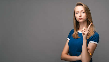Portrait of girl with blonde straight hair raises finger up, says: Attention please. Young female has serious confident look, isolated on gray background. Human emotions, facial expression concept.