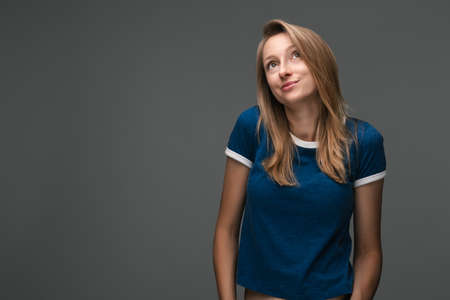 Studio shot of Good-looking woman with blonde straight hair wears blue t shirt, looks away enigmatically, wanting to do something illegally or secretly Stock fotó