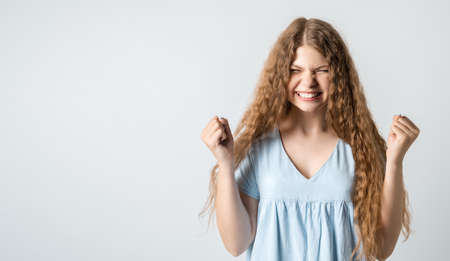 Life is wonderful. Joyful girl with curly long hair keeps fists clenched and exclaims in triumph, celebrates success, isolated over white background with blank space for your advertisement