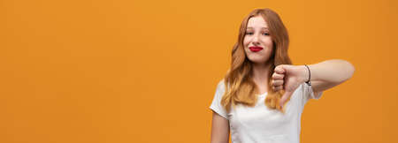 Pretty young woman with wavy redhead, wearing white t-shirt showing thumb down. Unlike, dislike, failure gestures concept, isolated on yellow background. Copy space for your text Banco de Imagens