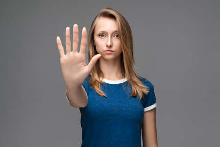Image of serious girl blonde straight hair in blue t shirt doing stop sign with palm of the hand. Warning expression on the face. Studio shot, gray background. Human emotions facial expression concept