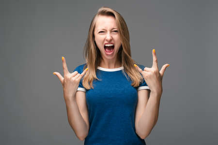 Emotive young female with blonde straight hair makes rock n roll sign, says I will rock this party, yells loudly, wears casual t shirt, feels self confident. Human emotions, facial expression concept Stock Photo