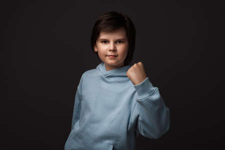 Image of Cute boy 10-12 years old, dressed in casual clothes smiling and making winner gesture, celebrating amazing news. Studio shot, gray background, isolated. Human emotions concept