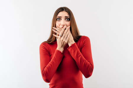 I'm afraid. Image of young scared woman with long chestnut hair in casual red sweater covering her mouth with hands. Fright, phobia, panic attack, horror and facial expression concept