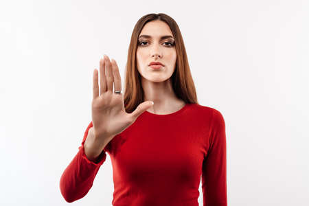 Image of serious woman with long chestnut hair in casual red sweater doing stop sign with palm of the hand. Warning expression on the face. Studio shot, white background. Human emotions concept