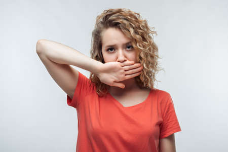 Image of blonde girl with curly hair in casual t shirt shutting mouth palm of the hand, promises to keep secret. Silence and secret concept. Studio shot, white background, isolated