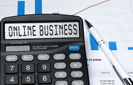Calculator with the word ONLINE BUSINESS on the display. Money, finance and business concept