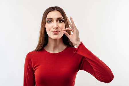 Young woman with long chestnut hair in casual red sweater, showing zip gesture as if shutting mouth on key, promises to keep secret, holds fingers near cheek. Silence and secret concept