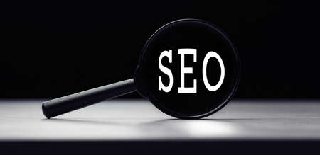 Magnifying glass with the word SEO - search engine optimization on table. Search idea