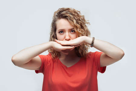 Image of blonde girl with curly hair in casual t shirt shutting mouth palms of the hand, promises to keep secret. Silence and secret concept. Studio shot, white background, isolated