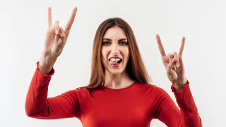 Image of excited woman with long chestnut hair in casual red sweater laughing and making horn gesture with fingers, says: I will rock this party. Human emotions concept. Studio shot, white background