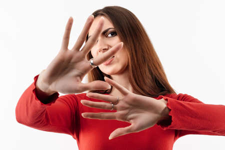 No way, stop doing. Image of dissatisfied girl with long chestnut hair in casual red sweater doing disgust face because aversion reaction with hands raised. Studio shot, white background Banco de Imagens
