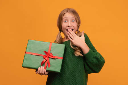 Image of charming blonde girl 12-14 years old in warm green sweater holding present box with red bow. Studio shot, yellow background, isolated. New Year Women's Day birthday holiday concept