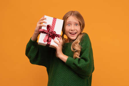 Image of charming blonde girl 12-14 years old in warm green sweater smiling and holding present box with red bow. Studio shot, yellow background. New Year Women's Day Birthday Holiday concept 版權商用圖片