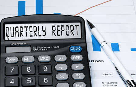 Calculator with the word quarterly report on the display. Money, finance and business concept