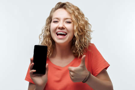 Young woman with curly hairstyle, dressed in casual t-shirt Showing Smartphone Blank Screen, looking at Camera Recommending Mobile App 版權商用圖片