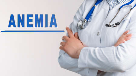 Text ANEMIA on a white background. Nearby is a doctor in white coat and stethoscope. Medical concept