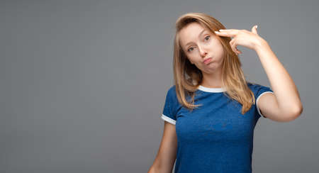 Funny young blonde female shoots in temple, tilts head, dressed in casual blue t shirt, demonstrates suicide gesture, isolated on gray background with blank space Archivio Fotografico