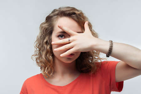 Portrait of frightened young woman with curly hair in casual t shirt covering her eyes with hands. Human emotions, facial expression concept. Studio shot, white background, isolated