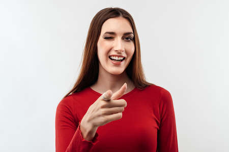 Pretty Young woman with long chestnut hair in casual red sweater hair looking at the camera and pointing her finger at you. Studio shot, white background. Human emotions, facial expression concept