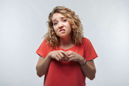 Shocked blonde girl with curly hair in casual t shirt expressing surprise on camera. Human emotions, facial expression concept. Studio shot, white background