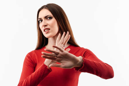 Image of dissatisfied girl with long chestnut hair in casual red sweater doing disgust face because aversion reaction with hands raised. Studio shot, white background. Facial expression concept